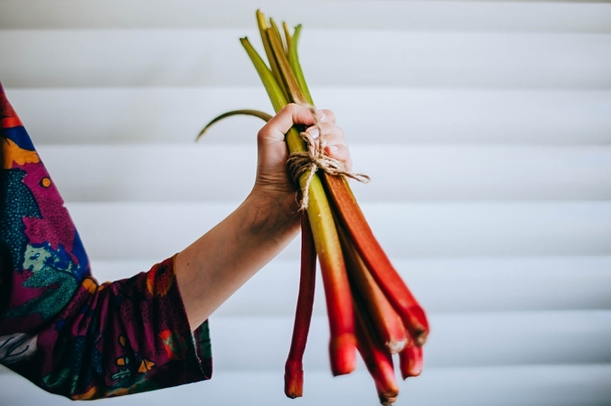 Close up of a woman holding a bunch of rhubarb