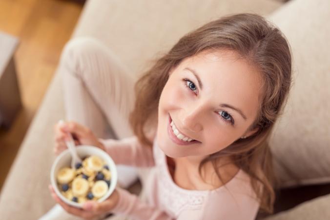 Close of up happy woman eating breakfast bowl of porridge and banana