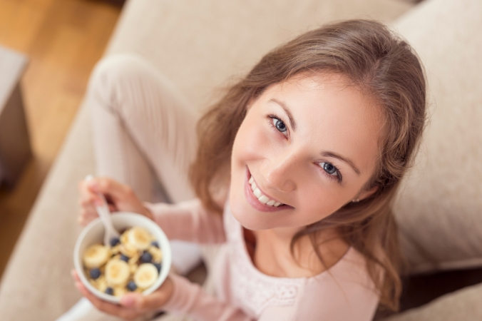 Close of up happy woman eating breakfast bowl of porridge and banana