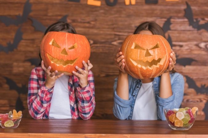 Two women holding jack-o-lantern pumpkins over their faces