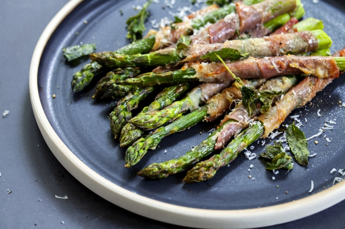 Roased asparagus wrapped in parma ham and sprinkled with parmesan cheese