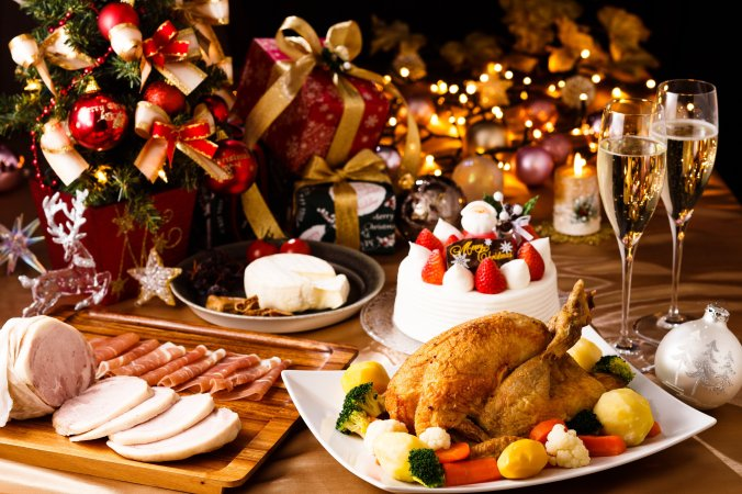 A table laid with christmas foods including turkey, cake, cheese and decorations