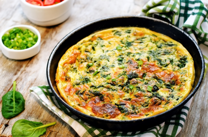 Spinach omelette in pan on breakfast table