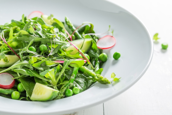 Close up of Spinach salad with peas, asparagus and radish