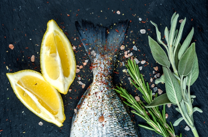 Trout with lemon wedges and herb