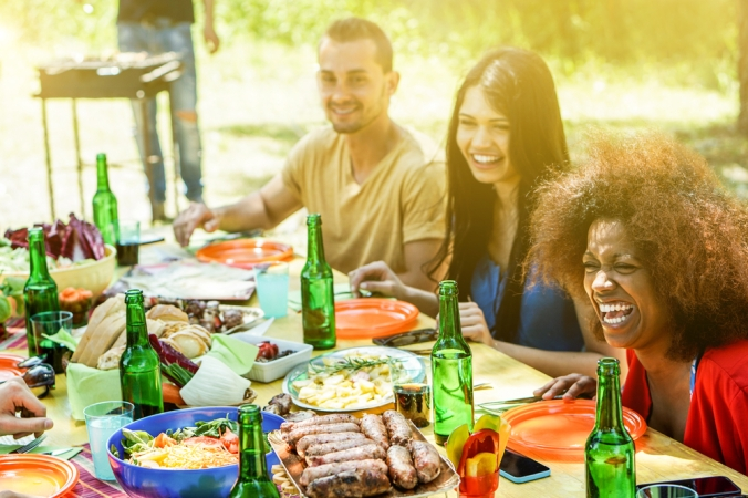 Group of friends enjoying eating a barbeque outside