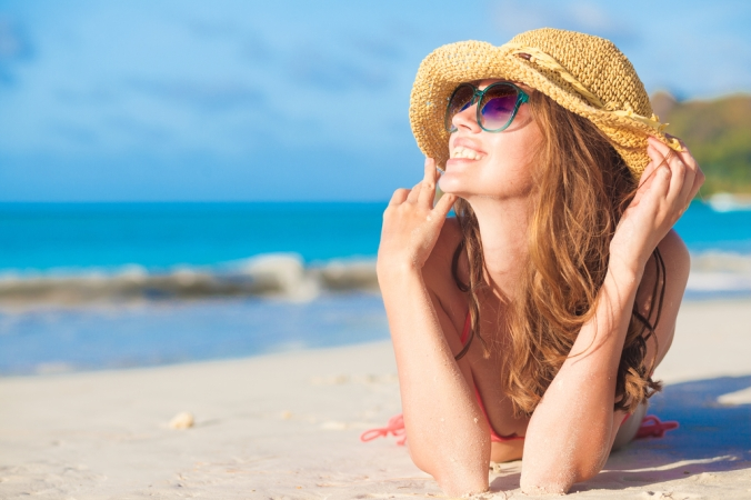 CLose up of smiling woman on the beach enjoying her holiday