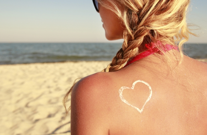 Close up of a woman's head and shoulder from behind on a beach to represent summer skin