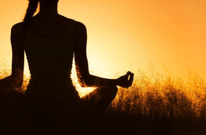 Close up on woman meditating in shadow with sunset background