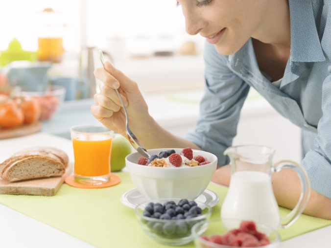 Woman eating a healthy breakfast with berries, yoghurt and orange juice