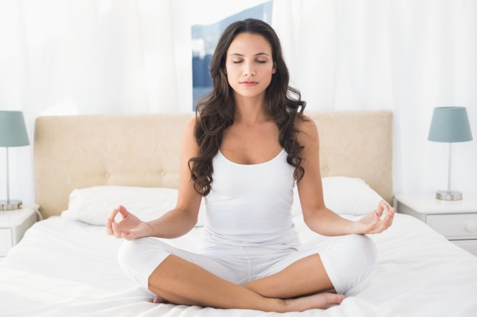 Woman with legs crossed sitting on bed meditating