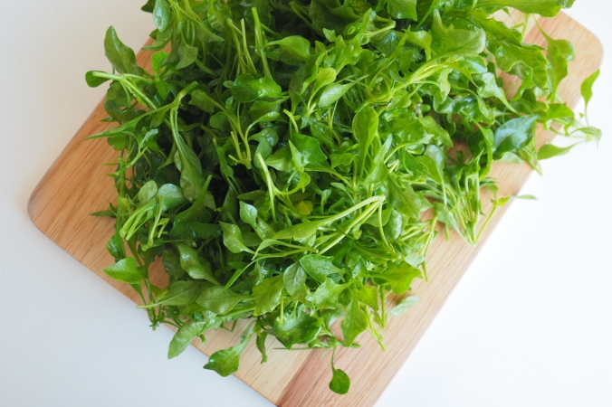 A bunch of watercress on a wooden board