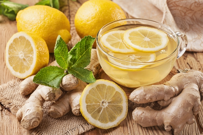 Fresh lemons and lemon tea with root ginger on a wooden background