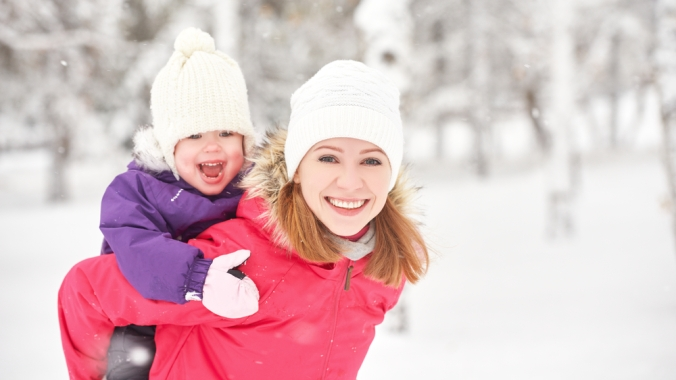 MOther and child on her back dressed up in hats and scarves on a winter walk in the snow