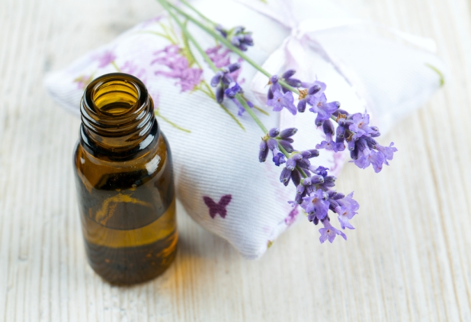 Lavender oil and fresh lavender on a pillow