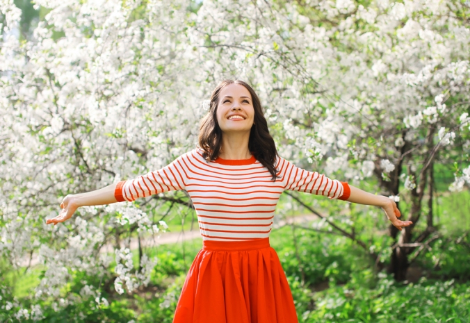A happy woman in from of a blossom tree showing spring time