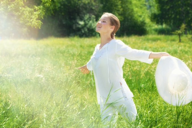 Happy woman in field showing spring time