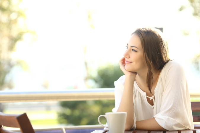 Relaxed woman looking happy sitting outside at a table overlooking a garden