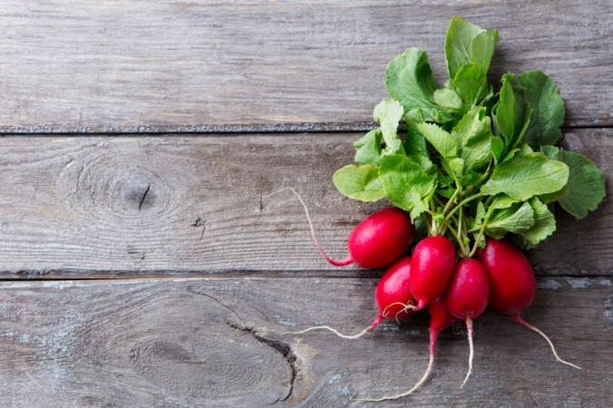 A bunch of radishes on a wooden background