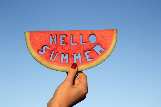 CLose up of a hand holding a slice of watermelow with the words hello summer cut out of it