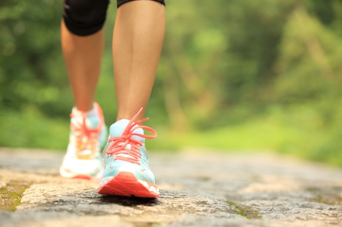 Close up on woman's trainers walking in forest