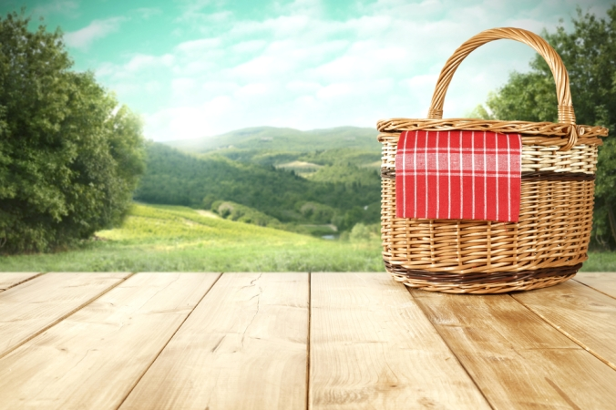 A picnic basket on a wodden table overlooking a beautiful countryside scene