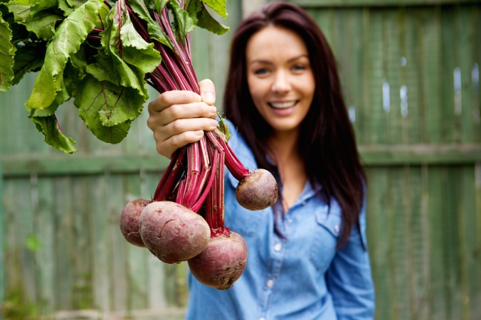 Woman holding up frshly grown beetroots