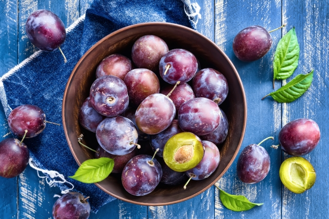 A bowl of plums on a blue wooden table
