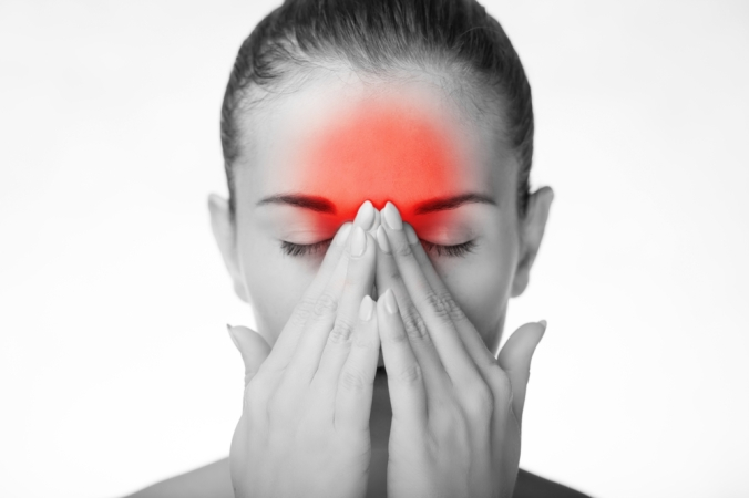 Close of woman in black and white with red pain showing in forehead to represent migraine attack