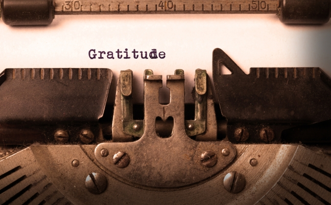 A close up of a typewriter with the word gratitude typed