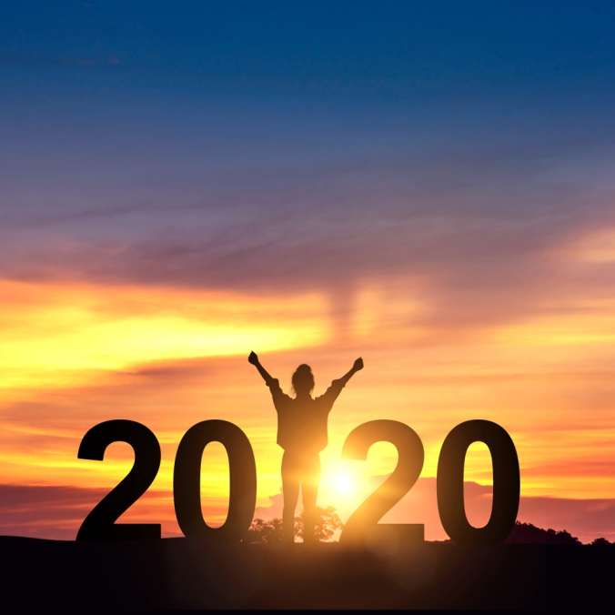 Woman with arms in the air with sunrise background and the number 2020 to represent the new year