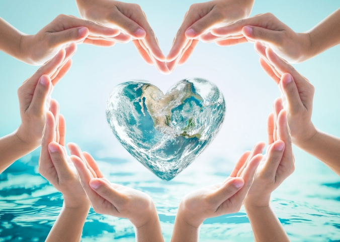 Hands surrounding a heart shaped world globe to represent kindness
