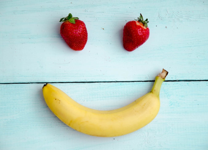 Two strawberries and a banana placed to make a smiley face