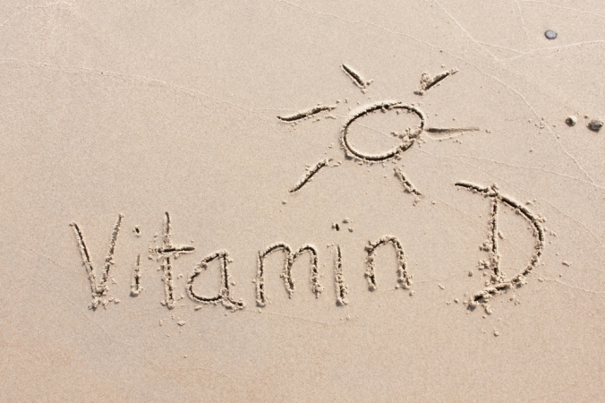Vitamin D and a sunshine symbol written in the sand