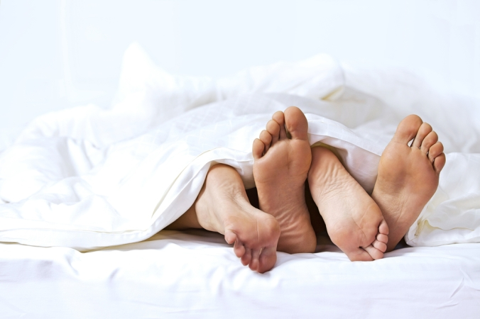 A couple's feet sticking out of the duvet to represent sex and libido