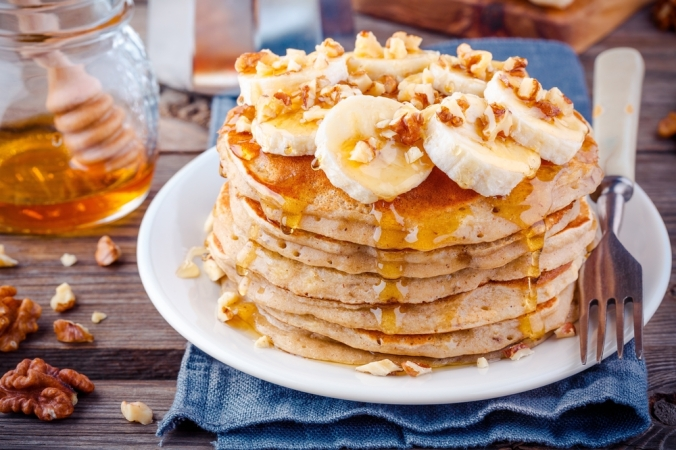 vegan pancakes topped with bananas and walnuts