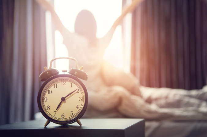 CLose up of an alarm clock and a woman getting out of bed to represent getting up at the same time every day