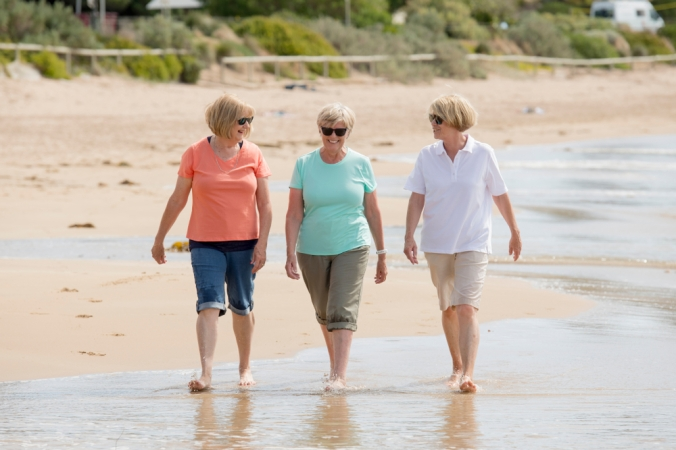 Group of retired women in their 60's walking on a beach