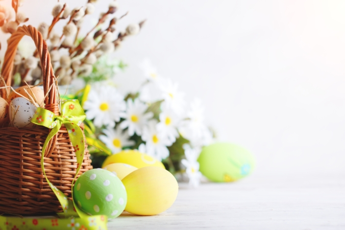 An easter basket fillwed with flowers and colourful decorated eggs