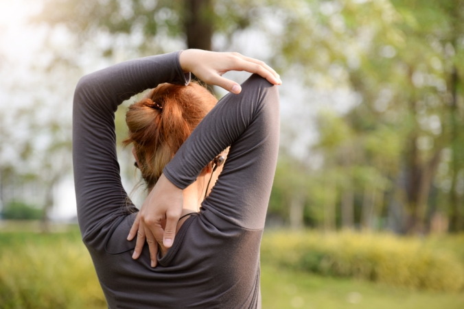 Close up of woman doing an arm stretch outdoors
