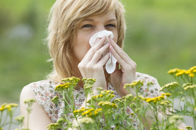CLose up of woman blwoing her nose surrounded by flowers to represent hay fever