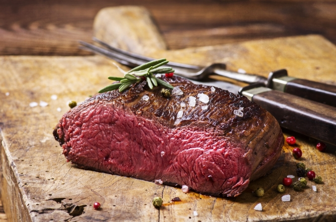 A cooked venison steak on a chopping board