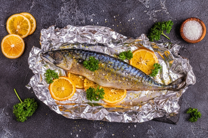 Fresh mackerel with lemon and herbs on foil ready to be baked