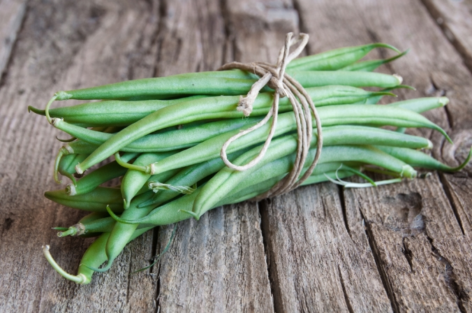 A bunch of runner beans on a wooden background
