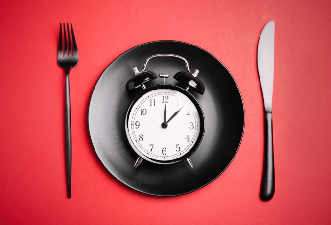 Alarm,Clock,,Plate,And,Cutlery,On,Red,Background,,Flat,Lay.