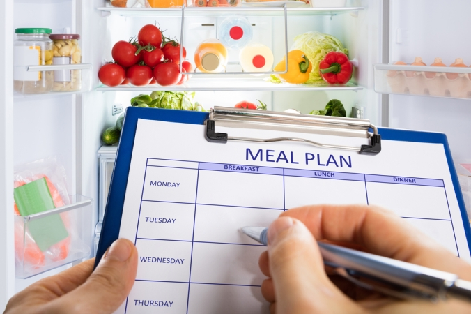 Person's,Hand,Filling,Meal,Plan,Form,On,Clipboard