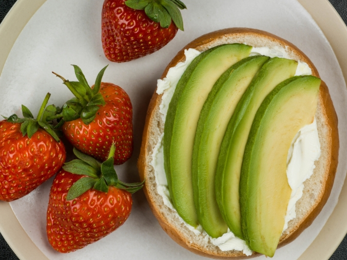 Cream,Cheese,And,Avocado,Bagel,Against,A,Black,Background