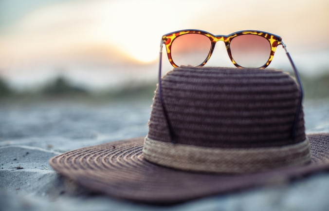 Hat,And,Glasses,Lie,On,A,Beach,At,A,Beautiful
